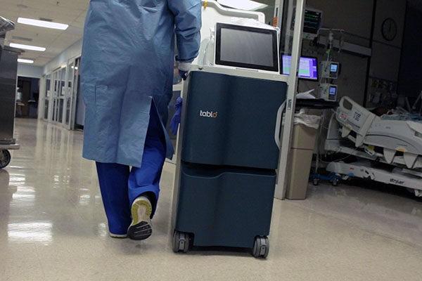 Nurse pushing Tablo dialysis machine